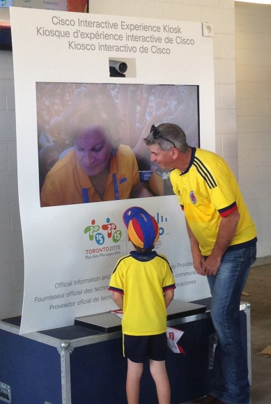 Colombia fans speak with a TO2015 volunteer through Cisco TelePresence before the women's Gold-medal soccer game.